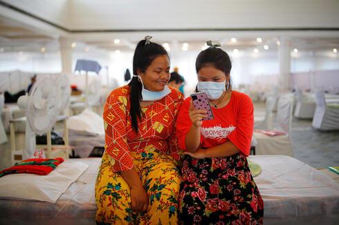 """Indian Jew girls, members of the Bnei Menashe, or the Children of Menashe, one of the """"lost tribes of Israel"""" from the India's northeastern state of Manipur, suffering from the coronavirus disease (COVID-19), look at a mobile phone at a COVID-19 care facility, inside a Gurudwara or a Sikh Temple, in New Delhi, India"""