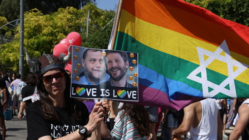 A woman at the recent Jerusalem Gay Pride Parade holds an image of extreme right-wingers Bentzi Gopstein and Bezalel Smotrich that depicts them as lovers (Photo: Amit Shabi)