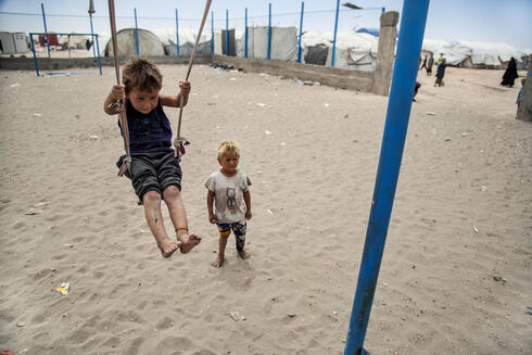 A boy plays on a swing at al-Hol camp, which houses families of members of the Islamic State group, in Hasakeh province, Syria, Saturday, May 1, 2021