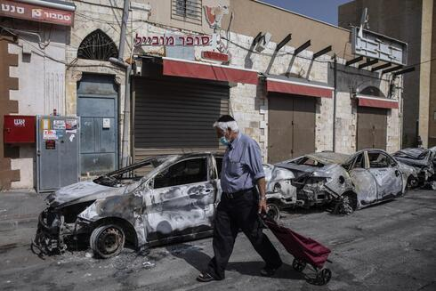 A man passes by cars torched after a night of violence between Israeli Arab protesters and Israeli police in the mixed Arab-Jewish town of Lod, central Israel, Tuesday, May 11, 2021