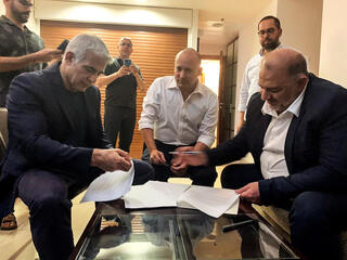 Ra'am leader Mansour Abbas, right, signing the coalition agreement with Yair Lapid, left, and Naftali Bennett that put an Arab party in the coalition for the first time in Israel's history
