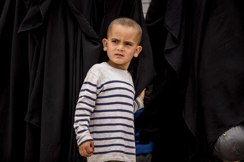 A boy stands next to his mother at al-Hol camp, which houses families of members of the Islamic State group, in Hasakeh province, Syria, Saturday, May 1, 2021