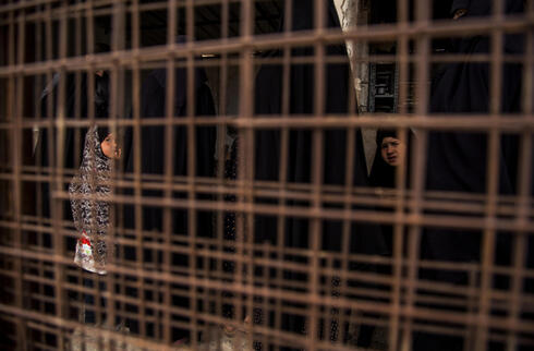 Two young girls are seen through a metal barrier, at al-Hol, which houses families of members of the Islamic State group, in Hasakeh province, Syria, Saturday, May 1, 2021