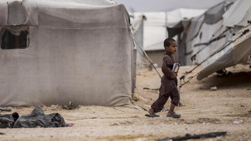 A boy holds a book as he walks at al-Hol camp, which houses families of members of the Islamic State group, in Hasakeh province, Syria, Saturday, May 1, 2021