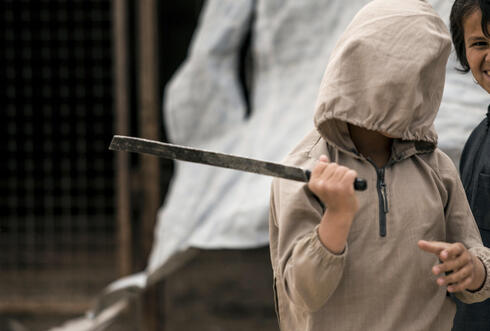A boy plays with a broken sword, at al-Hol camp, which houses families of members of the Islamic State group, in Hasakeh province, Syria, Saturday, May 1, 2021