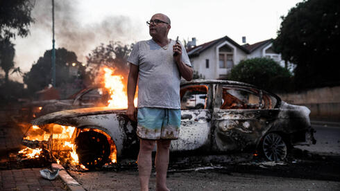 A local resident stands by his burning car during clashes between Israeli Arabs and police in Lod, May 11,2021