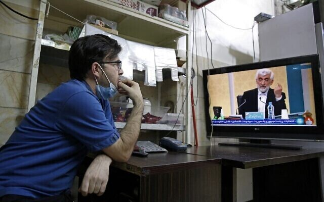 An Iranian vendor watches candidate Saeed Jalili speaking during the first televised debate between Iran presidential candidates, at a shop in Tehran
