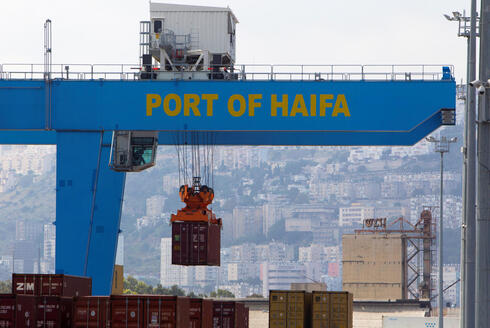 A crane unloads a container at the port of the northern city of Haifa