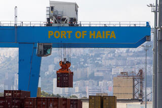 A crane unloads a container at Haifa port in northern Israel