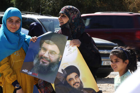Shiite Lebanese women hold portraits of Hasan Nasrallah, the leader of Lebanon's Hezbollah movement near the border with Israel in the southern Lebanese village of Adaisseh, on May 25, 2021