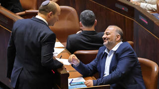 Prime Minister Naftali Bennett and Ra'am leader Mansour Abbas in the Knesset as their coalition was sworn in last month
