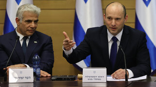 Prime Minister Naftali Bennett speaking at the opening of his government's first Cabinet meeting; to his left, Alternate Prime Minister and Foreign Minister Yair Lapid