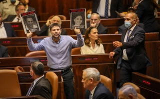 Religious Zionist leader Bezalel Smotrich holds up images of terror victims during Sunday's Knesset session to approve the new government