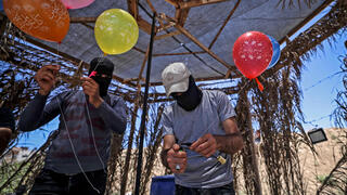 Masked members of Islamic Jihad prepare incendiary balloons to send into Israel from Gaza, June 15, 2021