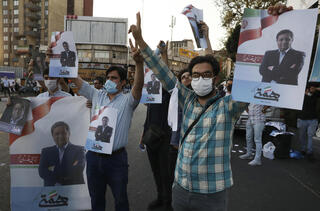 Supporters of Abdolnasser Hemmati, a presidential candidate in the June 18, elections, hold signs with his picture, during a street rally in Tehran, Iran, Tuesday, June 15, 2021