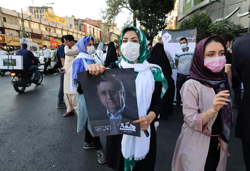 Hemmati supporter holds his portrait during a rally in the Iranian capital Tehran, June 15, 2021