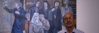 Palestinian artist Abed Abdi stands in front of his painting 'Refugees Waiting for Their Return' (2018) at the Haifa Museum of Art