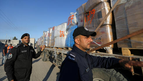 Palestinian police officers stand next to a truck carrying clothes for export at Kerem Shalom crossing in Rafah in the southern Gaza Strip,