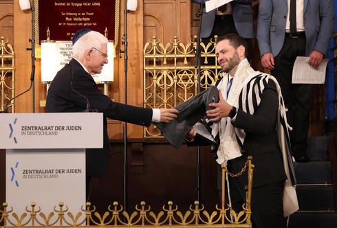 Josef Schuster (L), President of the Central Council of Jews in Germany, hands Rabbi Zsolt Balla a protective torah cover following the ceremony in which Balla was officially inaugurated as the first federal rabbi of the Bundeswehr, Germany's armed forces, at the main synagogue in Leipzig