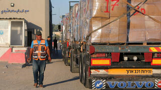 Palestinian man stands next to a truck carrying clothes for export, at Kerem Shalom crossing in Rafah in the southern Gaza Strip,