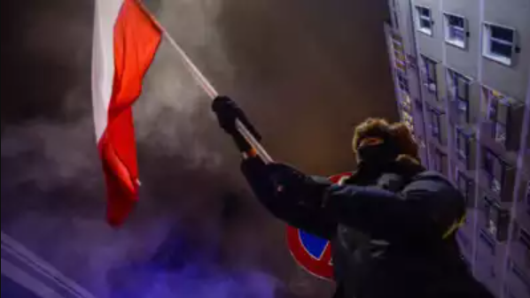 A person is waving the Polish flag during a protest