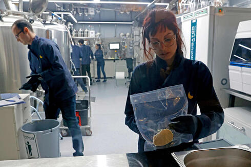 A technician holds a lab-grown chicken meat in a sealed bag at the food-tech startup SuperMeat in the central Israeli town of Ness Ziona