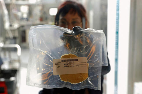 A technician displays a lab-grown chicken meat in a sealed bag at the food-tech startup SuperMeat in the central Israeli town of Ness Ziona