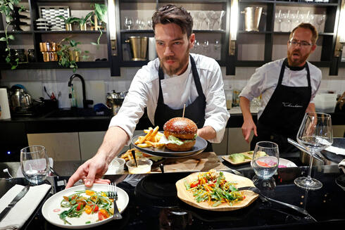 """Israeli Chef Shachar Yogev (C) serves burgers made with """"cultured chicken"""" meat"""
