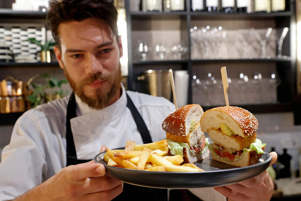 """Israeli Chef Shachar Yogev serves a burger made with """"cultured chicken"""" meat at a restaurant adjacent to the SuperMeat production site in the central Israeli town of Ness Ziona"""