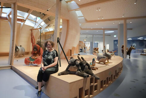 Ane Kleine-Engel, the head of the children's museum at the Jewish Museum pose for a photo as she is sitting between animals that are made out of recycled material, at the interactive exhibit about the story of Noah's Ark, in Berlin,