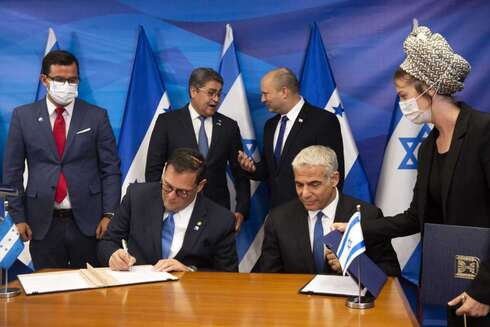 Prime Minister Naftali Bennett, back ceright, and Honduran President Juan Orlando Hernandez, speak as Israeli Foreign Minister Yair Lapid, front second right, and Honduran Foreign Minister Lisandro Rosales sign agreements between their two countries at the prime minister's office, in Jerusalem