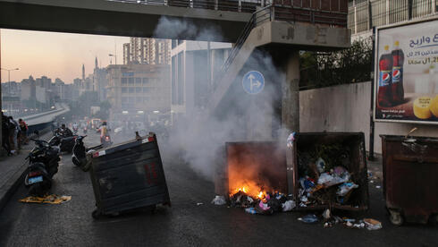 Anti-government protesters burn waste bins to block a highway that leads to the airport during a protest in Beirut, Lebanon, 26 June 2021