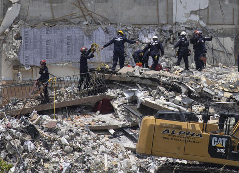 Rescue workers search in the rubble at the Champlain Towers South condominium in the Surfside area of Miami
