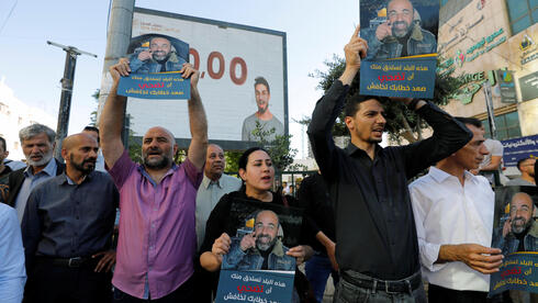 """Demonstrators holding placards protest over the death of Nizar Banat, a critic of the Palestinian Authority, in Hebron, in the Israeli-occupied West Bank, June 27, 2021. Placards read, """"This country deserves you to sacrifice, raise your voice and don't be afraid"""""""