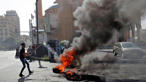 Lebanese forces watch anti-government protesters burn waste bins to block a highway that leads to the airport during a protest in Beirut, Lebanon, 26 June 2021
