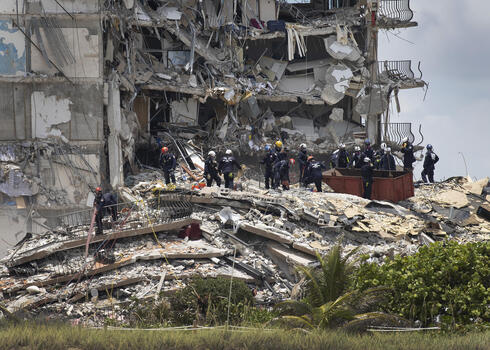: Members of the South Florida Urban Search and Rescue team look for possible survivors in the partially collapsed 12-story Champlain Towers South condo building on June 26, 2021