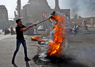 A demonstrator burning the Lebanese national flag during a protest in Beirut over the country's continued economic and political turmoil