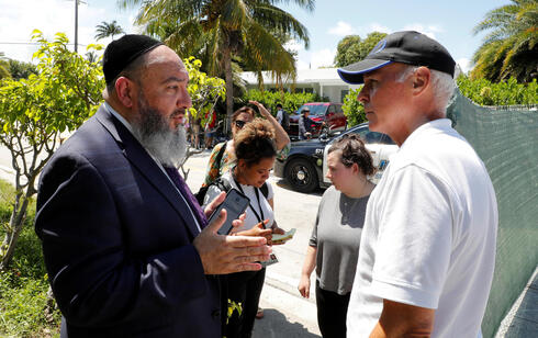 Rabbi Yosef Galimidi (L) speaks with Surfside Mayor Charles Burkett near the site of a partially collapsed residential building in Surfside, near Miami Beach, Florida, U.S. June 27, 2021