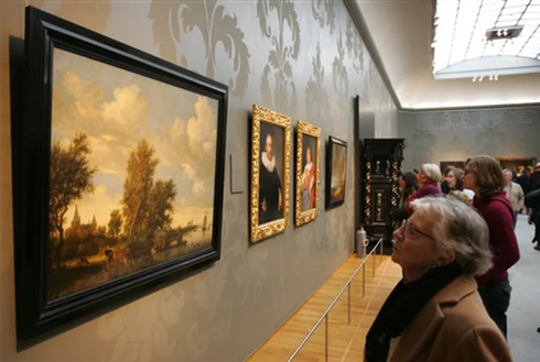 People look at a painting by Salomon van Ruysdael titled River Landscape with Ferry, left, at Rijksmuseum in Amsterdam, Netherlands, on February 4, 2006.