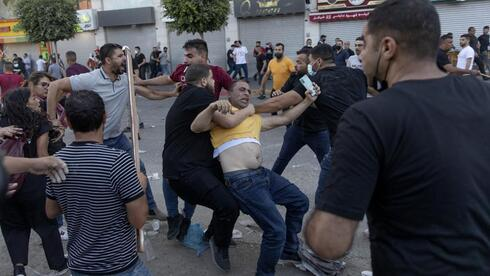 Palestinian security officers in plainclothes detain a demonstrator during clashes that erupted following a rally protesting the death of Palestinian Authority outspoken critic Nizar Banat, in the West Bank city of Ramallah, Saturday, June 26, 2021