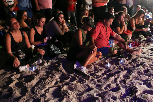 People attend a vigil in honor of residents of a partially collapsed residential building as the emergency crews continue search and rescue operations for survivors, in Surfside