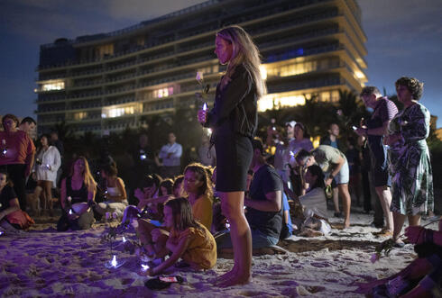 People join together in a community twilight vigil at site of collapsed building