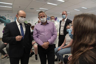 Prime Minister Naftali Bennett and Health Minister Nitzan Horowitz visiting a vaccination center in Holon last month
