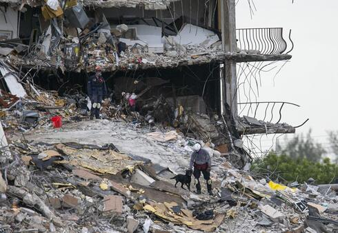 South Florida Urban Search and Rescue team look through rubble for survivors at the partially collapsed Champlain Towers South condo building in Surfside, Fla
