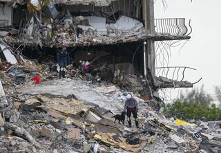 South Florida Urban Search and Rescue team look through rubble for survivors at the partially collapsed Champlain Towers South condo building in Surfside, Florida