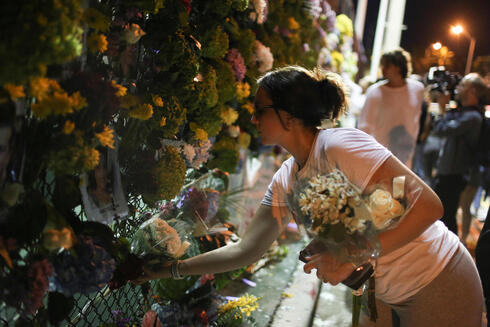 Awoman hangs flowers on a fence as people mourn at the memorial site created by neighbors in front of the partially collapsed building in Surfside on Monday