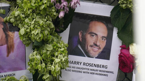 Image of Harry Rosenberg, missing since an oceanfront condo building collapsed in Surfside, Fla., hangs on a fence as part of a makeshift memorial