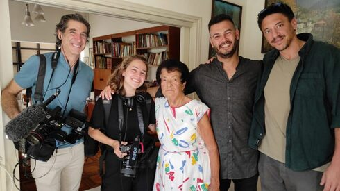 Uriya Rosenman, right, and Sameh Zakout, second from right, visit one of Zakout's Jewish neighbors in the mixed Arab and Jewish city of Ramla during taping for a documentary