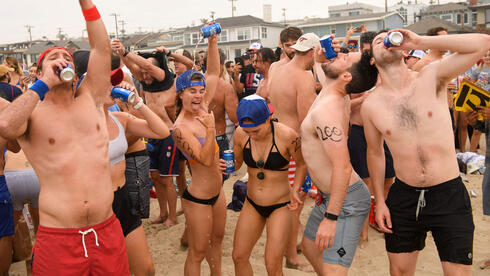 Participants chug beer on the beach during the 47th annual Hermosa Beach Ironman competition where participants must run a mile, paddle a surfboard a mile, and chug a six-pack of beer on July 4, 2021 in Hermosa Beach, California