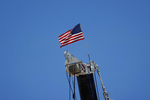 An American flag flutters atop a crane at the site of a partially collapsed residential building